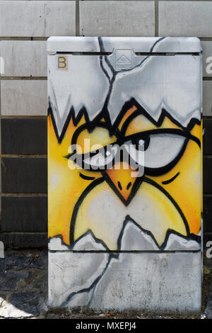 An unknown artist has done this beautiful and funny graffiti on a junction box in the city of Cologne. It shows a hatching chick. - Stock Photo