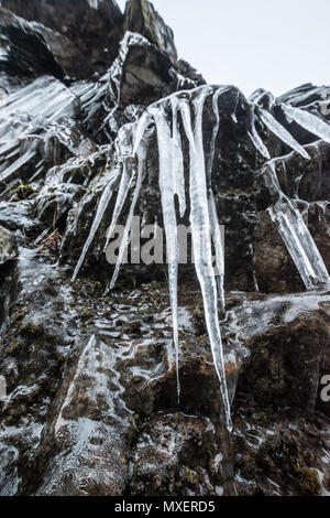 Icicle hanging from rock wall - Stock Photo