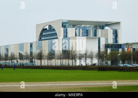 Berlin, Germany - April 14, 2018: Side view of Federal Chancellery building with green grass on the foreground under the overcast sky - Stock Photo