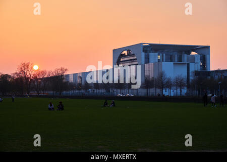 Berlin, Germany - April 14, 2018: Side view of Federal Chancellery building with people on the lawn in the evening - Stock Photo