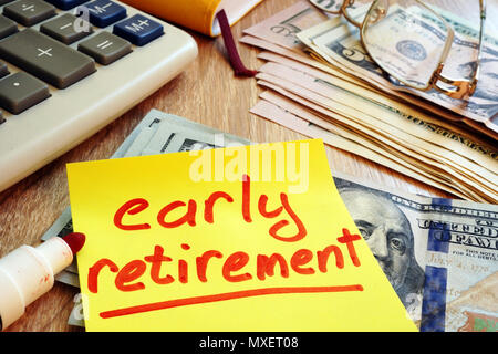Early retirement written on a memo stick and savings. - Stock Photo