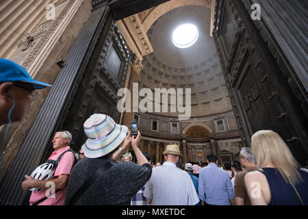 Rome Pantheon interior, light true the hole on dome, tourists visiting - Stock Photo