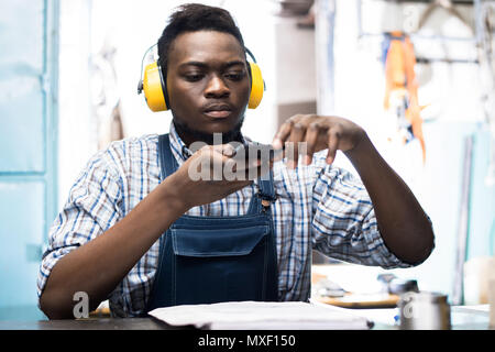 Lathe Operator Using Smartphone - Stock Photo