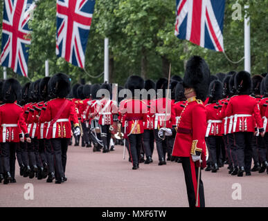 Soldiers marching down The Mall, London during Trooping the Colour parade to mark the Queen`s birthday. Soldier standing to attention at front. - Stock Photo