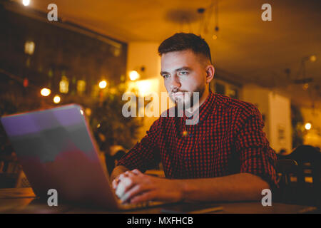 A young handsome Caucasian man with beard and toothy smile in a red checkered shirt is working behind a gray laptop sitting at a wooden table. Hands on the keyboard. In the evening at the coffee shop - Stock Photo