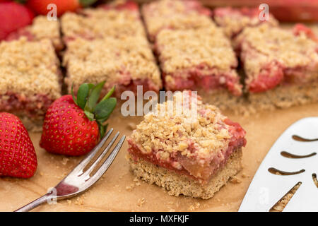 Delicious and healthy summer snack or dessert.  Homemade gluten-free rhubarb and strawberry crumble slice, made with fresh fruit. - Stock Photo