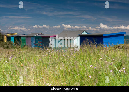 A row of brightly coloured beach huts at bembridge duvet on the Isle of Wight with an interesting cloud formation above on a hot weather summers day. - Stock Photo