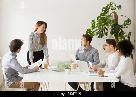 Female business coach making presentation to workers - Stock Photo