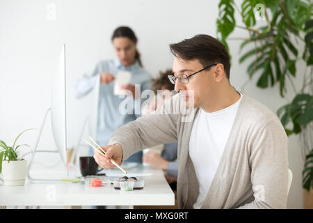 Middle aged worker eating sushi during office work break - Stock Photo