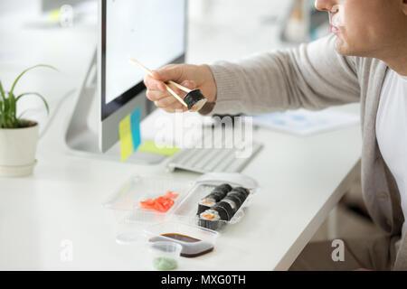 Close up of male employee enjoying sushi at workplace - Stock Photo