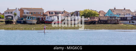 Shoreham-By-Sea; 3rd June 2018; Panorama of Female on a Paddle Board Passing Houseboats on a Riverbank - Stock Photo