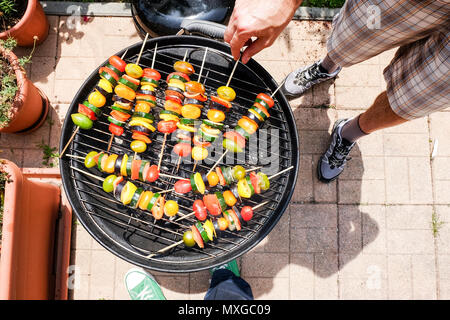 Cooking and grilling vegetables - zucchini tomato and pepeer - skewers on a barbecue outdoors a sunny relaxed weekend - Stock Photo
