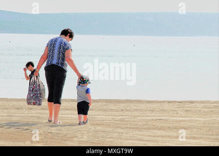 Weymouth. 4th June 2018. UK Weather: By chance alignment, this woman on Weymouth beach appears to be carrying a youngster in her shopping basket ! Credit: stuart fretwell/Alamy Live News - Stock Photo