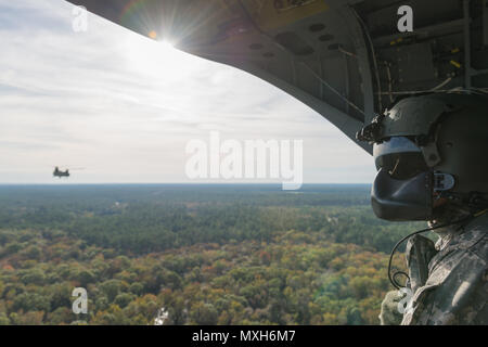 A U.S. Army Chinook crewmember assigned to the 3rd Combat Aviation Brigade observes Chinooks in flight over Fort Stewart during a slingload training mission at Hunter Army Airfield, Nov. 6, 2016. The soldiers are transporting howitzers to a training area on Fort Stewart in support of the 3rd Division Artillery. (U.S. Army photo by Lt. Col. Brian J. Fickel) - Stock Photo
