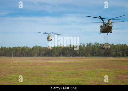 Two Chinooks assigned to 3rd Combat Aviation Briade transport Humvees and artilley pieces during a slingload training mission at Fort Stewart, Nov 6, 2016. (U.S. Army photo by Lt. Col. Brian J. Fickel) - Stock Photo