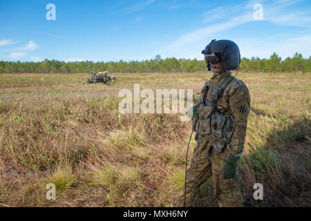 A U.S. Army Chinook crewmember assigned to 3rd Combat Aviation Brigade observes soldiers from 3rd Division Artillery emplace artillery pieces on at a training site on Fort Stewart, 6 Nov 2016. (U.S. Army photo by Lt. Col. Brian J. Fickel) - Stock Photo