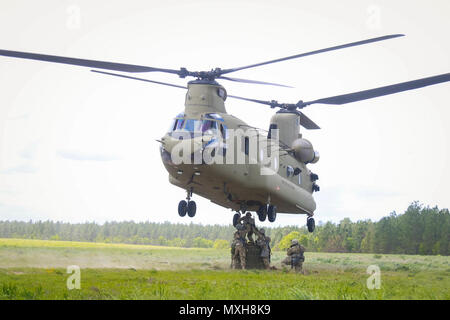 Soldiers assigned to 1st Battalion, 319th Airborne Field Artillery Regiment, 82nd Airborne Division Artillery attach an ammo container to the belly of a CH-47F Chinook helicopter from 3rd General Support Aviation Battalion, 82nd Combat Aviation Brigade during sling load operations on Fort Bragg, N.C., May 4. - Stock Photo