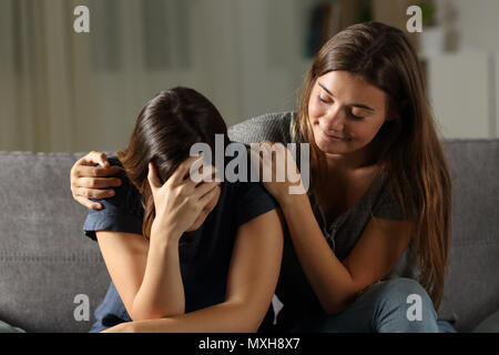 Bad hypocrite friend comforting a sad girl sitting on a couch in the living room at home - Stock Photo