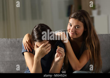 Hypocrite friend comforting a divorced wife sitting on a couch in the living room at home - Stock Photo