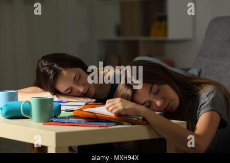 Two tired students sleeping over notebooks after studying late hours in the night at home - Stock Photo