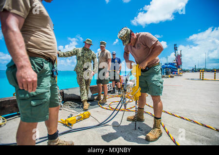 Chief Petty Officer Dan Luberto, right, assigned to Underwater Construction Team (UCT) 2's Construction Dive Detachment Bravo (CDDB), tests a hydraulic hammer drill in Diego Garcia, British Indian Ocean Territory, Nov. 7, 2016.  CDDB is performing precision underwater demolition and light salvage to remove obstructions from Diego Garcia's deep draft wharf. CDDB is on the third stop of their deployment, where they are conducting inspection, maintenance, and repair of various underwater and waterfront facilities while under Commander, Task Force (CTF) 75, the primary expeditionary task force res - Stock Photo