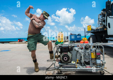 Chief Petty Officer Scott Schleisman, assigned to Underwater Construction Team (UCT) 2's Construction Dive Detachment Bravo (CDDB), starts an air compressor in Diego Garcia, British Indian Ocean Territory, Nov. 7, 2016. CDDB is performing precision underwater demolition and light salvage to remove obstructions from Diego Garcia's deep draft wharf. CDDB is on the third stop of their deployment, where they are conducting inspection, maintenance, and repair of various underwater and waterfront facilities while under Commander, Task Force (CTF) 75, the primary expeditionary task force responsible  - Stock Photo