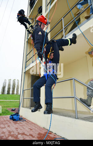 Firefighters Damon Favor and Sara Munaretto assigned to U.S. Army Garrison Italy, practice rappelling at the Army Training Command tower, 34 feet high, during Department of Defense Technical Rope Rescue 1, at Caserma Ederle, Vicenza, Italy, Nov. 10, 2016. Firefighters here received training from instructors of 435th Construction and Training Squadron, Ramstein Air Base, Germany. Training consisted of a variety of rescue techniques and scenarios including operational risk management, incident management system, ground support for helicopter operations and confined space rescue. This training is - Stock Photo