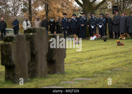Leaders from the 52nd Fighter Wing, Spangdahlem Air Base, Germany, and German citizens pause during a German National Day of Mourning observance ceremony at the Kolmeshöhe Military Cemetery in Bitburg, Germany, Nov. 13, 2016. The day, known as Volkstrauertag in German, observes the human cost of war and was established following the conclusion of the First World War. (U.S. Air Force photo by Staff Sgt. Joe W. McFadden) - Stock Photo