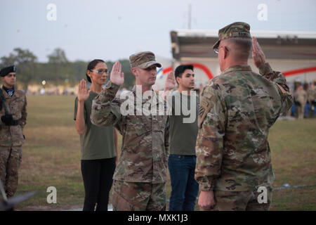 Maj. Gen. Jim Rainey, commanding general of 3rd Infantry Division reenists soldiers assigned to Fort Stewart during Twilight Tattoo Nov. 15, 2016. Twilight Tattoo is a ceremony honoring veterans and family members. (Photo by LTC Brian J. Fickel) - Stock Photo