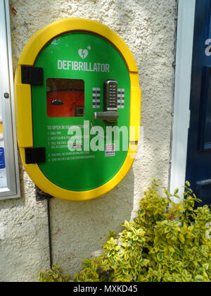 Public emergency defibrillator mounted on the wall of the community center at Shincliffe, County Durham, England. - Stock Photo