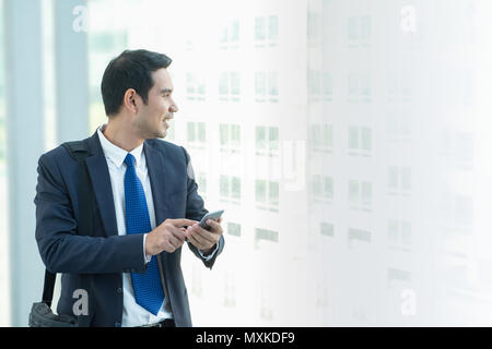 Business man walking and using mobile phone to chatting with friend after work at corridor office building - Stock Photo