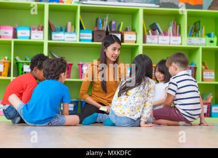 Asian female teacher teaching mixed race diversity group of kids reading book sitting on library floor in classroom,Kindergarten pre school concept - Stock Photo
