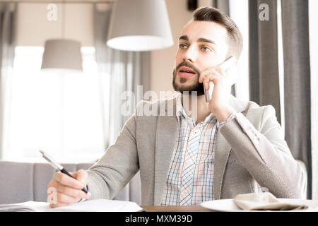 Modern bearded businessman working in cafe - Stock Photo