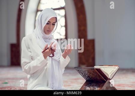 Young beautiful Muslim Woman Praying In Mosque - Stock Photo