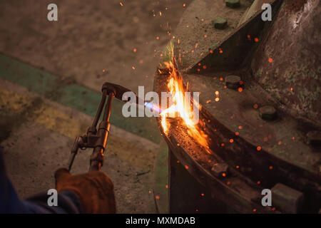 Metal cutting with acetylene and oxygen gas torch. Soft focus due to high ISO and shallow Depth Of Field - Stock Photo