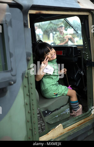 An Okinawa resident poses inside a Humvee Nov. 20, 2016 during the Japan Ground Self Defense Force Festival on Camp Naha, Okinawa, Japan. The festival celebrated the 6th anniversary of the 15th Brigade and the 44th anniversary of Camp Naha. Marines with Combat Assault Battalion, 3rd Marine Division, III Marine Expeditionary Force brought the Humvee, a Light Armored Vehicle and an Assault Amphibious Vehicle for display. Attendees of the festival were able to take photos with the Marines and their vehicles. (U.S. Marine Corps photo by Cpl. Jessica Collins) - Stock Photo