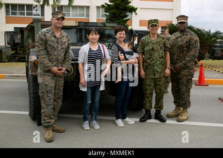 A family poses with Marines and a Japan Ground Self Defense Force service member next to a Humvee Nov. 20, 2016 during the JGSDF Festival on Camp Naha, Okinawa, Japan. The festival celebrated the 6th anniversary of the 15th brigade and the 44th anniversary of Camp Naha. Marines with Combat Assault Battalion, 3rd Marine Division, III Marine Expeditionary Force brought the Humvee, a Light Armored Vehicle and an Assault Amphibious Vehicle for display. Attendees of the festival were able to take photos with the Marines and their vehicles.  (U.S. Marine Corps photo by Cpl. Jessica Collins) - Stock Photo