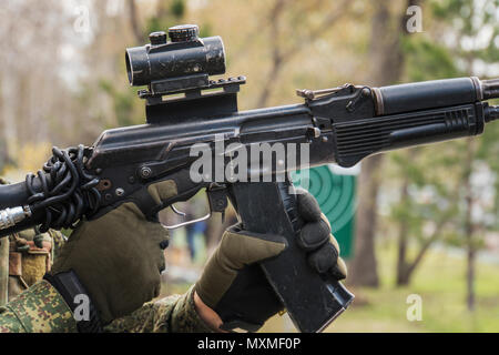 man aiming with an AK-47 with reflex sight, separatist. Male mags in the Kalashnikov. reloading the rifle. clip replacement. Practice shooting. Traini - Stock Photo