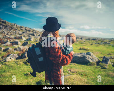 A young mother with a baby and a big bacpack is trekking through the wilderness - Stock Photo