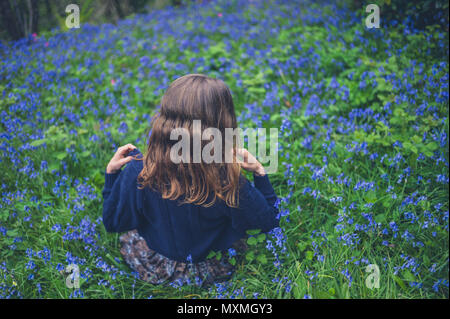 A young woman is sitting in a meadow of bluebells - Stock Photo