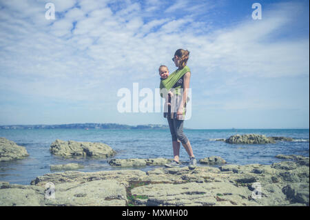A young mother is walking on the coast with her baby in a sling - Stock Photo