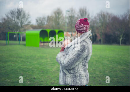 A young mother is standing on the grass in a park in winter with her baby in a carrier sling - Stock Photo