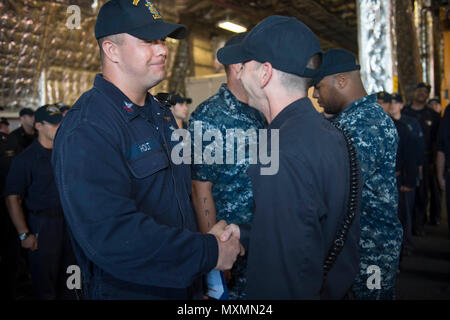 161117-N-MW990-013 CHANGI NAVAL BASE, Singapore (November 17, 2016) Petty Officer 2nd Class Thomas Scarborough, right, pins Petty Officer 1st Class Walter Holt, left, with the Enlisted Aviation Warfare Specialist (EAWS) device aboard USS Coronado (LCS 4). Holt is one of two sailors to be the first to receive his EAWS aboard an LCS. Currently on a rotational deployment in support of the Asia-Pacific Rebalance, Coronado is a fast and agile warship tailor-made to patrol the region's littorals and work hull-to-hull with partner navies, providing 7th Fleet with the flexible capabilities it needs no