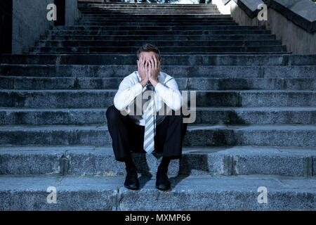 young business man crying abandoned lost in depression sitting on the street stairs suffering emotional pain, sadness in a mental health concept photo - Stock Photo