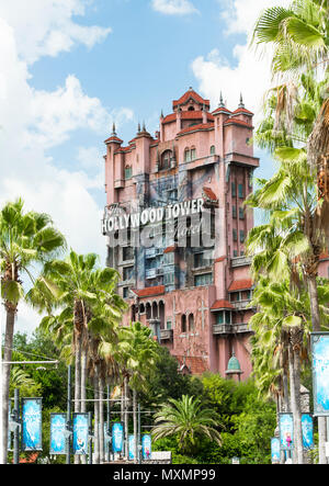 Hollywood Tower in Disney Hollywood Studios in Orlando Florida. This shot is framed by an avenue of green palm trees, blue sky and fluffy white clouds - Stock Photo