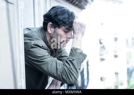 close up portrait of sad and depressed man looking out the window on a balcony at home suffering depression and felling lonely in mental health concep - Stock Photo