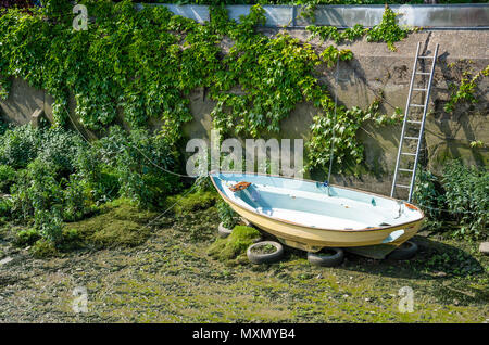 A boat is beached on the muddy river bed during low tide on The River Thames. - Stock Photo