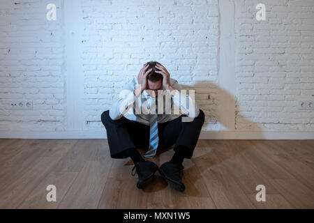 depressed business man feeling sad, lonely and suffering from anxiety leaning on a white wall at home in mental health depression concept - Stock Photo