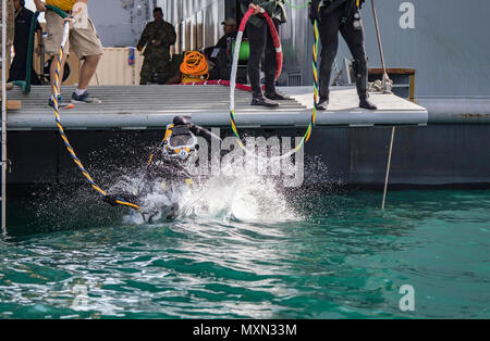 A U.S. Army engineer diver with the 511th Engineer Dive Detachment from Fort Eustis, Va., jumps off the MG Charles P. Gross (Logistics Support Vessel-5) and into the Arabian Gulf, off the coast of Kuwait Naval Base, to practice diving procedures Nov. 18, 2016. The two week training exercise, Operation Deep Blue, required Army divers to practice their diving procedures and react to underwater emergency scenarios. (U.S. Army photo by Sgt. Angela Lorden) - Stock Photo