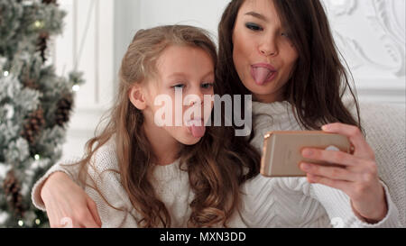 Cheerful young mother and her daughter making comic xmas selfies and showing tongues - Stock Photo